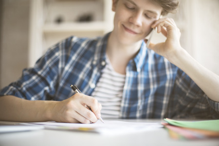 essay: Smiling young man doing paperwork while talking on mobile phone at office desk.