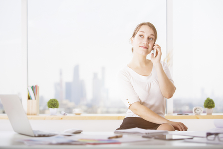 Portrait of attractive european businesswoman talking on phone in modern office interior