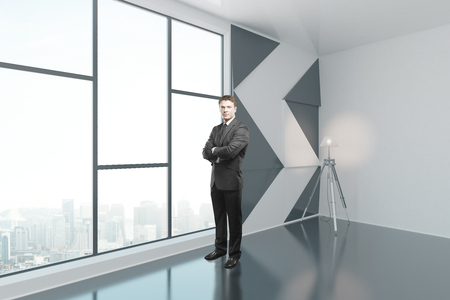 window view: Businessman standing in interior with patterned black-and-white wall, floor lamp and window with city view. Side view, 3D Rendering