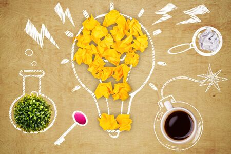 Top view of wooden desk with creative and abstract crumpled paper lightbulb, coffee cup bomb, plant test-tube, eraser key and magnifier. Idea concept
