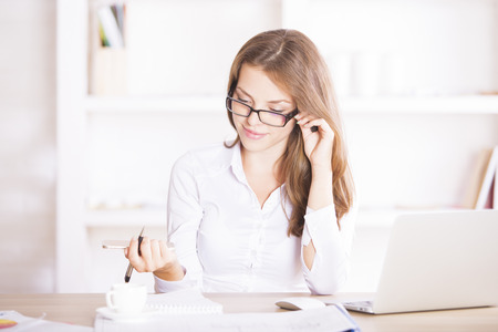 Portrait of smiling young woman dealing with paperwork at modern office desk with coffee cup, laptop computer and other items