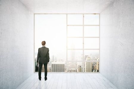 looking at view: Businessman looking out of big window in interior with concrete walls, white wooden floor and city view. Research concept. 3D Rendering Stock Photo