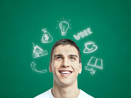 jovenes felices: Feliz el hombre joven que piensa en futuro trabajo, la educación y el crecimiento económico en el fondo pizarra