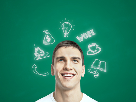 estate planning: Happy young man thinking about future job, education and financial growth on chalkboard background Stock Photo