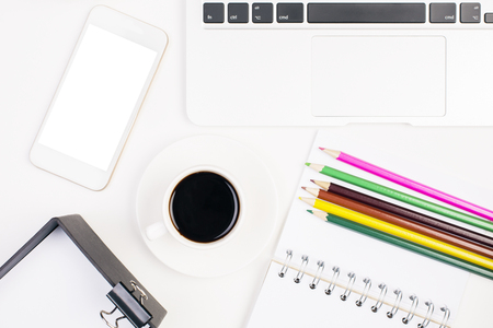 stationery items: Top view of office table with blank white smartphone, coffee cup, laptop keyabord and stationery items. Mock up