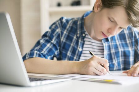 essay: Close up of casual guy doing homework at desk with blurry laptop. White brick wall and shelves in the background
