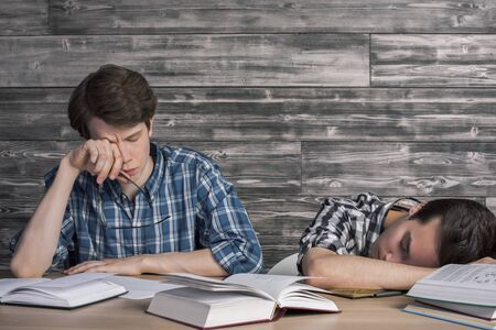 tired: Two young college students tired of studying at wooden table with many open books. Textured wooden wall in the background