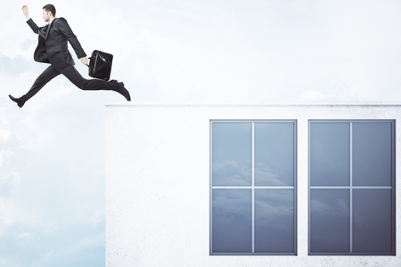 roof windows: Businessman with briefcase jumping off roof of concrete building with windows and blank wall on sky background. Success concept. Mock up, 3D Rendering Stock Photo