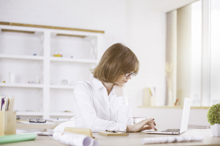 modern businesswoman: Businesswoman using laptop on messy desktop with supplies and other items in modern office interior Stock Photo