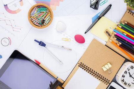 stationery items: Top view of messy office workplace with blank tablet, clock and various colorful stationery items. Mock up Stock Photo