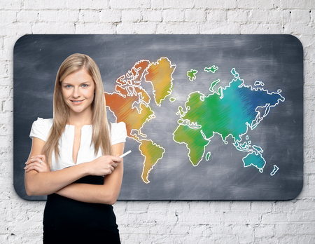 businesswoman standing: Businesswoman standing against chalkboard with colorful map hanging on white brick wall. Travel concept