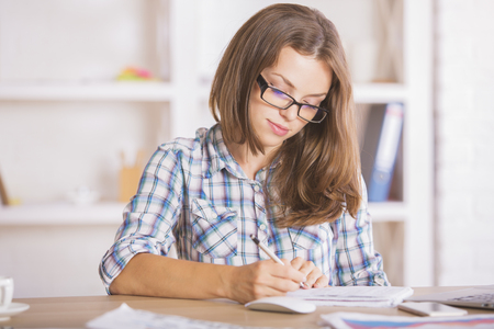 modern businesswoman: Young caucasian businesswoman doing paperwork at modern bright workplace Stock Photo