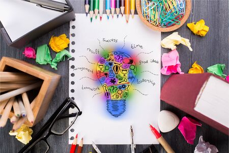 Top view of messy desktop with colorful supplies, glasses and abstract lightbulb sketch in spiral notepad. Creative idea concept