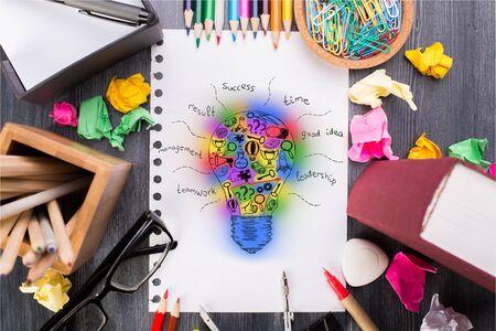 oficina desordenada: Vista superior del escritorio desordenado con las fuentes de colores, gafas y boceto bombilla resumen en el cuaderno de espiral. el concepto de idea creativa Foto de archivo