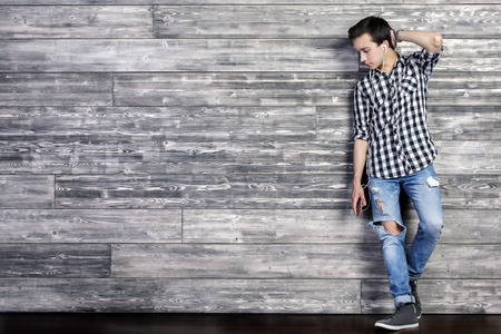niño parado: Handsome young guy listening to music on textured dark wooden wall background with copy space. Full length