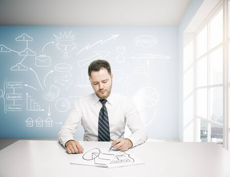 Businessman doing paperwork in bright office interior with business sketch on board Stock Photo
