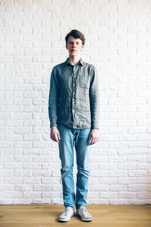 niño parado: Casually dressed young guy standing in studio with white brick wall and wooden floor