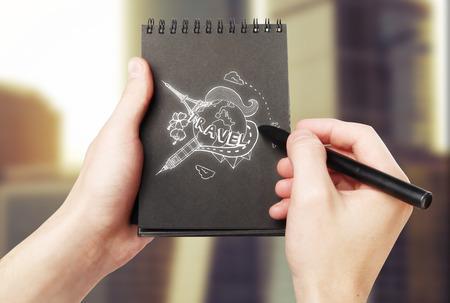 globe terrestre dessin: Homme mains dessin esquisse Voyage dans le bloc-notes en spirale noir sur fond flou.