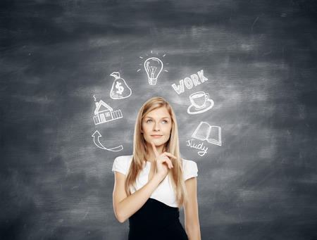 Pensive young business woman thinking about future job, education and financial growth on chalkboard background
