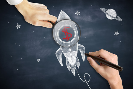 stock market launch: Male hands drawing and holding magnifier over space ship sketch with red dollar sign.