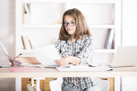 casually dressed: Portrait of casually dressed young businesswoman doing paperwork at workplace Stock Photo
