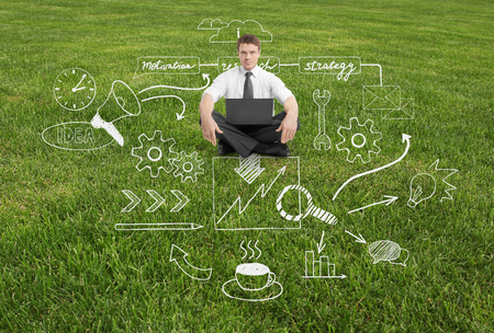 laptop outside: Businessman with laptop sitting on grass with abstract business sketch Stock Photo