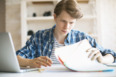 Close up of casual young man doing his assignment at desk with blurry laptop. White brick wall and shelves in the background Stock Photo