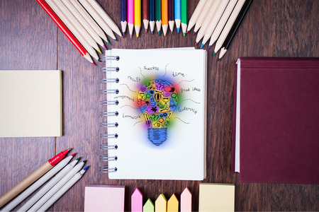 idea sketch: Top view of wooden tabletop with colorful supplies and abstract lightbulb sketch in spiral notepad. Creative idea concept Stock Photo