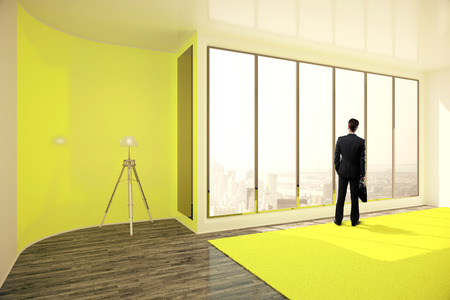standing lamp: Businessman with briefcase standing in bright yellow interior with floor lamp, window with city view and daylight. 3D Rendering Stock Photo