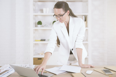Attractive young woman using laptop while standing at wooden office desk with smartphone, paperwork and other items