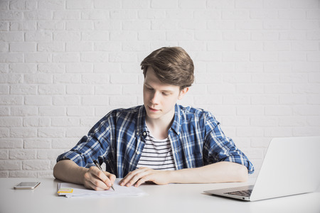 Concentrated young businessman doing paperwork at office desk with laptop and smartphone on white brick wall background