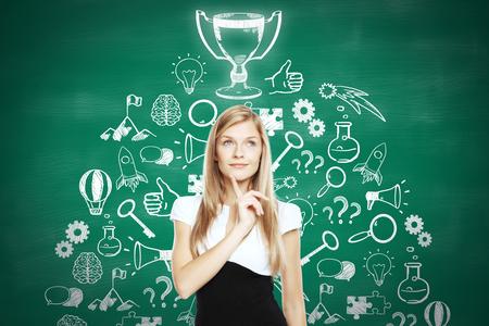 competencia: Empresaria reflexiva de pie contra la pizarra con la taza del ganador y los iconos de los negocios de boceto. Concepto de líder empresarial
