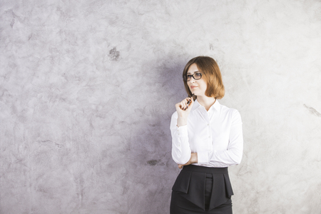 woman  glasses: Attractive smiling woman in formal outfit against concrete wall with copy space Stock Photo