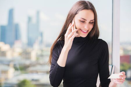 orden de compra: Portrait of gorgeous european businesslady making purchase order by cellular phone on blurry city background