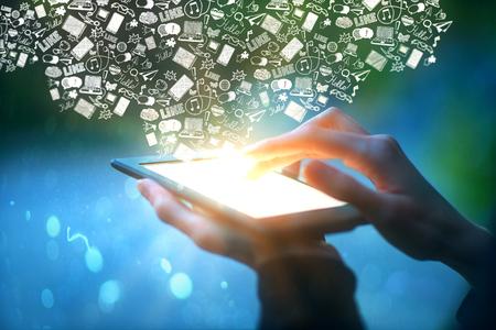 Primo piano delle mani maschile tiene e toccando schermo illuminato della tavoletta digitale con icone di comunicazione astratte su sfondo blu. Concetto sociale dei media