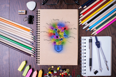 idea sketch: Top view of wooden desktop with colorful supplies and abstract lightbulb sketch in spiral notepad. Creative idea concept Stock Photo