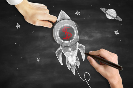 stock market launch: Male hands drawing and holding magnifier over rocket ship sketh with red dollar sign. Blackboard background. Start up concept