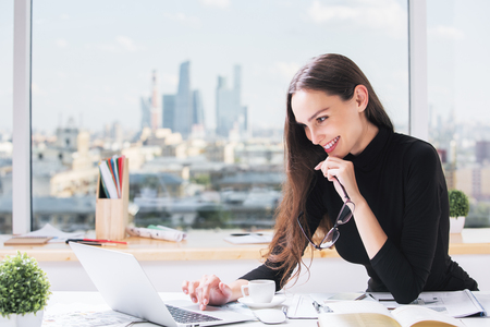 Portrait of attractive young businesswoman using laptop at office desk with coffee cup, paperwork and other items. City view in the background