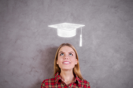 woman looking up: Portrait of attractive young woman looking up at mortarboard sketch on concrete wall. Graduation concept Stock Photo