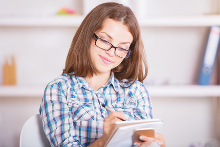 Portrait of attractive young woman with smartphone in hand writing in notepad