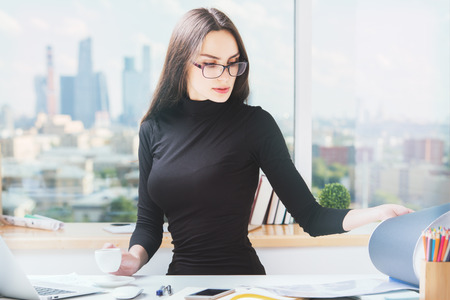 young beautiful woman: Portrait of beautiful young business woman doing paperwork in bright office with panoramic city view Stock Photo