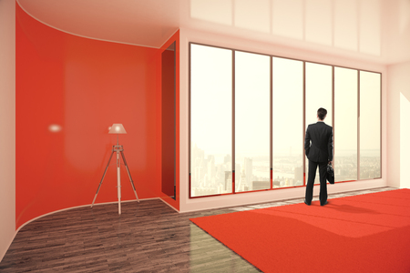 standing lamp: Businessman with briefcase standing in bright red interior with floor lamp, window with city view and daylight. 3D Rendering Stock Photo
