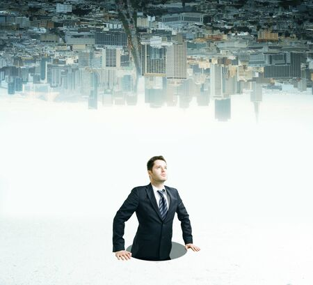 Businessman inside hole looking up on upside down city background Stock Photo
