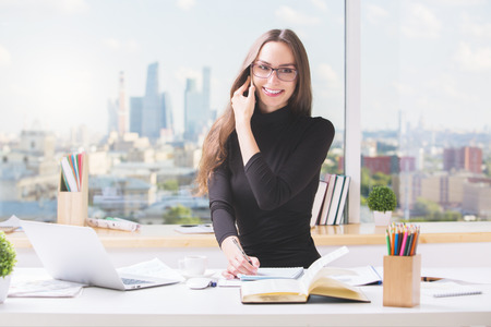 Portrait of happy european businesswoman at office desk talking on cellular phone and doing paperwork. Blurry city view in the background Reklamní fotografie