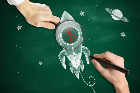 stock market launch: Male hands drawing and holding magnifier over space ship sketh with red dollar sign. Green chalkboard background. Start up concept