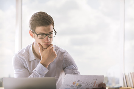 Young businessman in glasses reading documentation in bright office Imagens