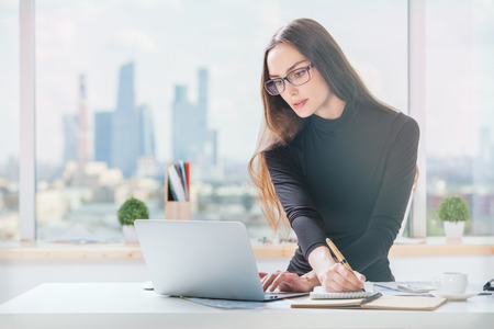 Portrait of concentrated young businesslady working on project in bright office with panoramic city view and sunlight