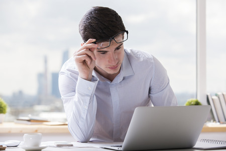 Portrait of handsome caucasian guy using notebook computer at office desk with coffee cup, paperwork and other items. Blurry city background