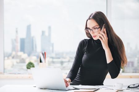 Portret van charmante Europese businesslady bij bureau die op cellulaire telefoon spreken en laptop computer met behulp van. Wazig uitzicht op de stad op de achtergrond