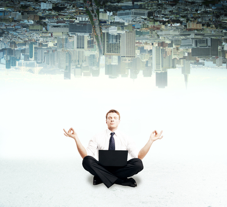 Businessman with laptop meditating on upside down city background Stock Photo